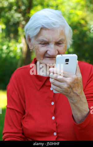 Beautiful elderly woman looking at a smartphone - Stock Photo