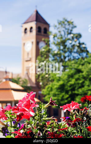 Alabama Tuskegee Macon County Courthouse clock tower exterior trees 19th century Romanesque Revival style flowers - Stock Photo