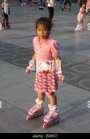 Little Vietnamese girl on inline skates in a park in Hanoi, Vietnam. - Stock Photo