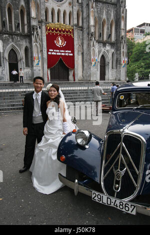 A wedding couple poses with a 1950s Citroen Traction Avant car in front of St Joseph's Cathedral, Hanoi, Vietnam - Stock Photo