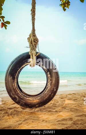 Old tyre swing on tropical beach - Stock Photo