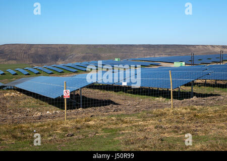 SolarPark next to Opencast coal mine showing clean green energy of solar power contrasting with destructive open - Stock Photo