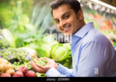 Closeup portrait, handsome young man in blue shirt picking up green brussel sprouts, choosing vegetables in grocery - Stock Photo
