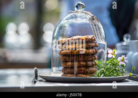 junk food, culinary, baking and unhealthy eating concept - close up of cookies chocolate  and muesli bars in glass - Stock Photo