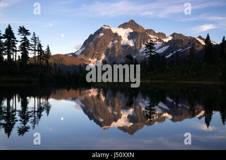 Light hits Mt Shuksan well at sunset above picture lake - Stock Photo