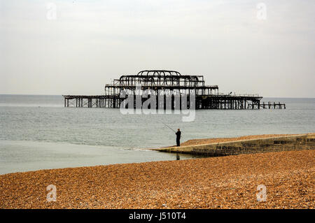 The remains of the burned out West Pier, with a man fishing off  the pebble beach, Brighton - Stock Photo