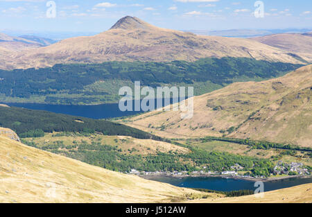 The forested slopes of Ben Lomond mountain rise from the shores of Loch Lomond lake, beyond Arrochar village, in - Stock Photo