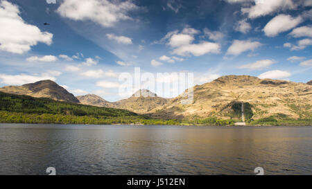Mountains rise from the banks of Loch Lomond in the West Highlands of Scotland. - Stock Photo