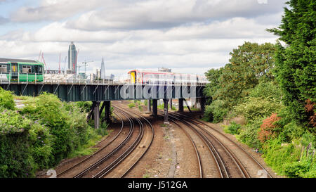 London, England, UK - June 14, 2014: A Southern commuter train and Gatwick Express passenger train cross a flyover - Stock Photo