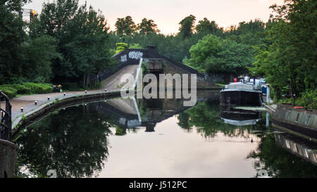 A bridge reflected in the waters of the Grand Union Canal at Ladbroke Grove in west London. - Stock Photo
