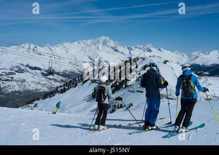 Skiers about to descend to Montchavin les Coches with Mont Blanc in the distance, French alps. - Stock Photo
