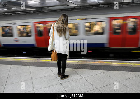 Back view of a young woman standing on underground station platform with speeding train passing on opposite side - Stock Photo