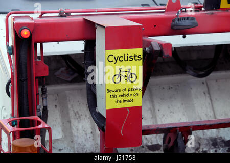Sign on back of recycling lorry for cyclists to beware passing the truck vehicle on inside next to the curb to avoid - Stock Photo