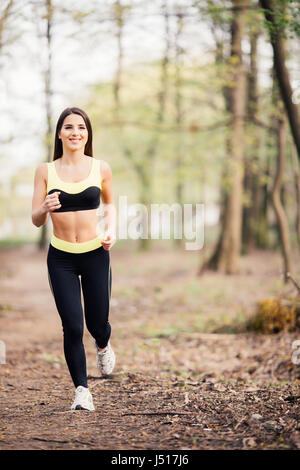 Young lady running. Woman runner running through the spring park road. Workout in a Park. Beautiful fit Girl. Fitness - Stock Photo