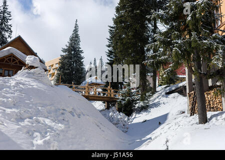 Wooden bridge in a snow-covered skiing town on a sunny winter day - Stock Photo