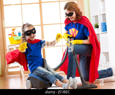 Child and mother dressed as superheroes using vacuum cleaner in room. Family middle-aged woman and daughter have - Stock Photo