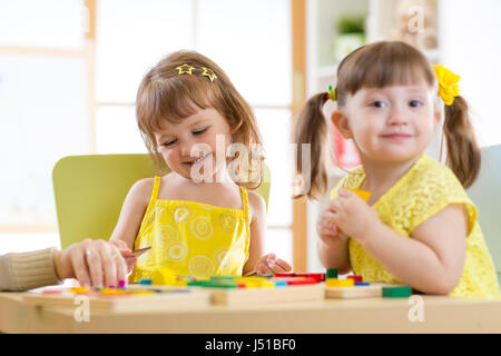 Kids children girls playing with educational child toys at home or daycare centre. - Stock Photo