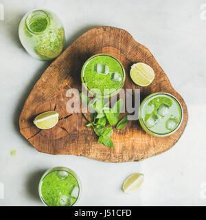 Fresh green smoothie in bottle and glasses with ice cubes, mint and lime on wooden board over grey marble background, - Stock Photo