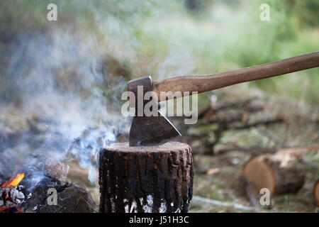 Axe in tree stump and campfire with smoke in summer forest - Stock Photo
