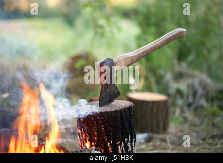Axe in tree stump and campfire with smoke in summer forest at sun evening - Stock Photo