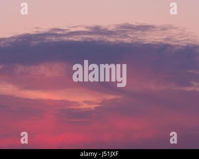 dark magenta clouds at sundown in springtime - Stock Photo