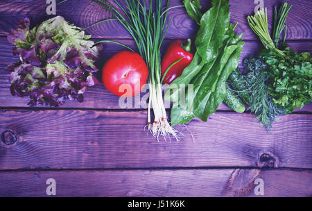 Fresh tomato vegetables, cucumber, onion and lettuce on a brown wooden surface, empty space at the bottom, vintage - Stock Photo