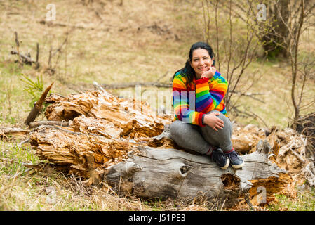 Cheerful female sitting on a bark tree in nature - Stock Photo
