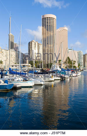 Sail boats docked at the Waikiki Yacht Club in the Ala Wai Harbor with the Hawaii Prince Hotel in the background. - Stock Photo