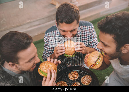 High angle view of three young men eating fresh hamburgers above grill - Stock Photo