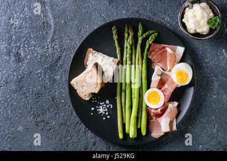 Cooked green asparagus with half boiled egg, sliced bread, butter and ham bacon served with sea salt on black ceramic - Stock Photo