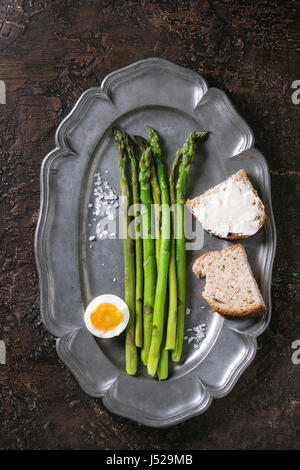 Cooked green asparagus with half boiled egg and sliced bread served with sea salt on vintage metal plate over brown - Stock Photo