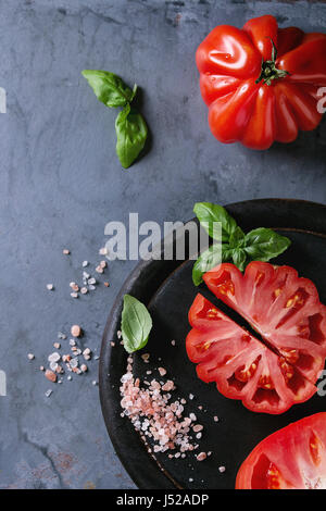 Whole and sliced organic tomatoes Coeur De Boeuf. Beefsteak tomato with pink salt and basil on black wooden chopping - Stock Photo
