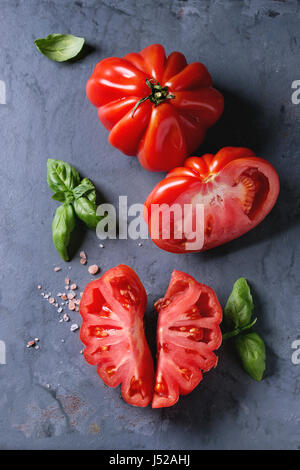 Whole and sliced organic tomatoes Coeur De Boeuf. Beefsteak tomato with pink salt and basil on blue gray metal texture - Stock Photo