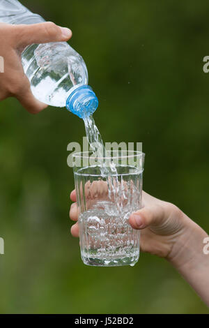 hand of adult pouring clean water from bottle into glass of child on the green blurred background - Stock Photo