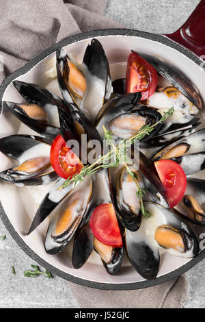 Cooked mussels in a pan served on a napkin garnished with tomatoes and thyme. Steamed mussels in white wine sauce. - Stock Photo