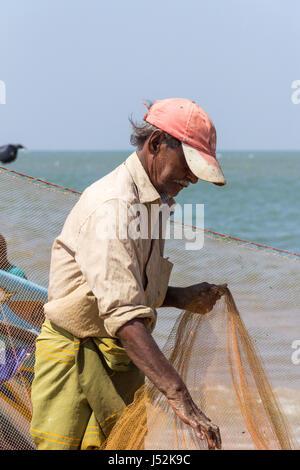 Fishermen folding his nets on Negombo beach, Sri Lanka - Stock Photo