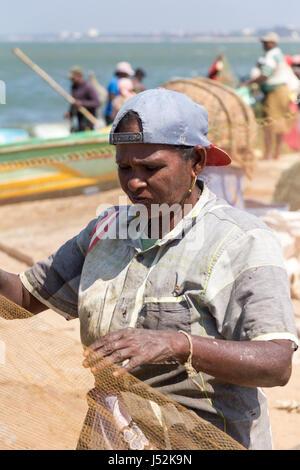 Woman folding nets  on Negombo beach, Sri Lanka - Stock Photo
