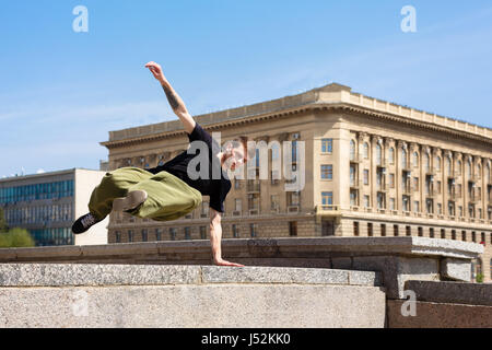 Young man jumping over the wall. Parkour in the urban space. Sport in the city. Sport activity. - Stock Photo
