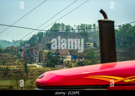 Nepali countryside with a smoke stack of a truck and power lines. - Stock Photo