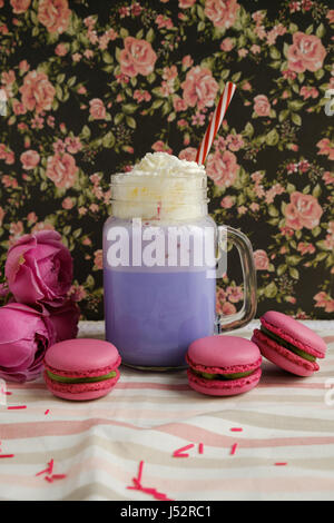 Purple coffee in stylized mason jar cup with macarons and roses and colorful decoration on background of floral - Stock Photo