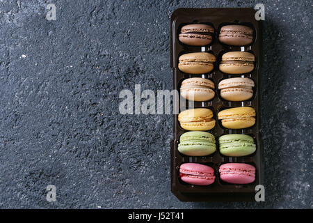 Variety of colorful french sweet dessert macaron with different fillings in balck plastic box over dark stone texture - Stock Photo