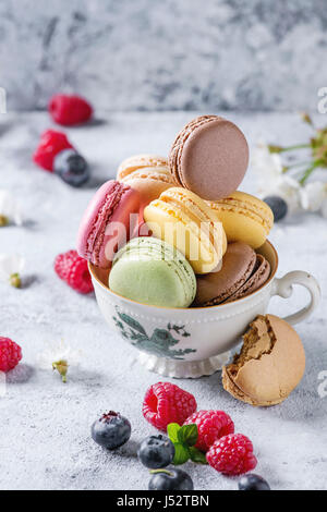 Variety of colorful french sweet dessert macarons with different fillings served in vintage tea cup with spring - Stock Photo