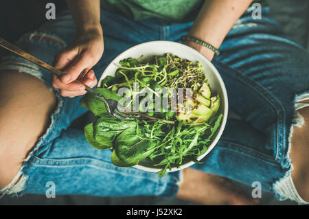 Green vegan breakfast meal in bowl with spinach, arugula, avocado, seeds and sprouts. Girl in jeans holding fork - Stock Photo