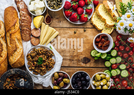Olive tapenade, sausages, baby corns, french baguette, cheese, capers, strawberries, corn bread slices, sun-dried - Stock Photo