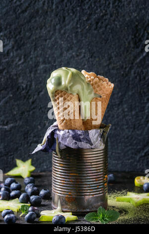 Waffle cones of Green tea matcha soft elastic ice cream with mint leaves, carambola, lime, blueberries in old tin - Stock Photo
