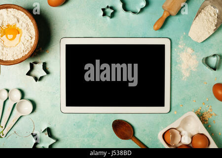 Baking background with flour, eggs, kitchen tools and tablet computer on blue rustic table. Top view. Flat lay style. - Stock Photo