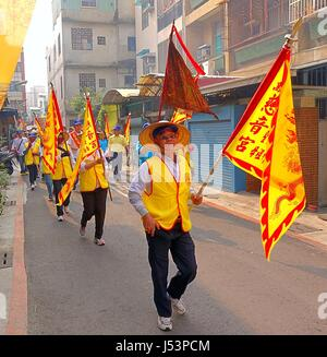 KAOHSIUNG, TAIWAN -- MARCH 16, 2014: Religious devotees in yellow vests carry flags in a procession that is part - Stock Photo