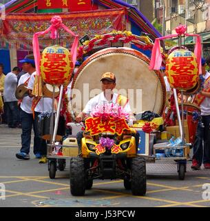 KAOHSIUNG, TAIWAN -- MARCH 16, 2014: An unidentified man drives a small tractor that pulls a large ceremonial drum - Stock Photo