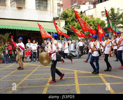 KAOHSIUNG, TAIWAN -- MARCH 16, 2014: Religious devotees carry flags and beat gongs in a procession that is part - Stock Photo