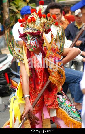 KAOHSIUNG, TAIWAN -- MARCH 16, 2014: A young man with painted facial mask and dressed up as an ancient warrior poses - Stock Photo